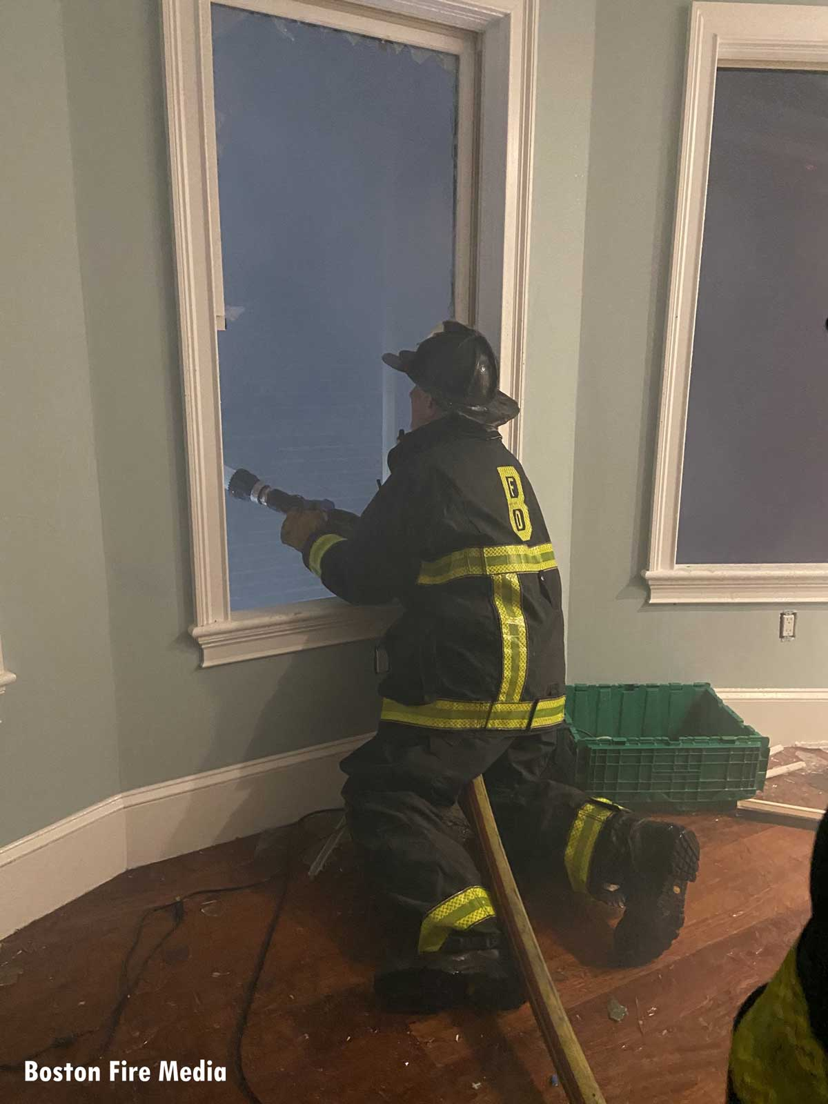 A firefighter on the interior of a dwelling directs a hose stream through a window