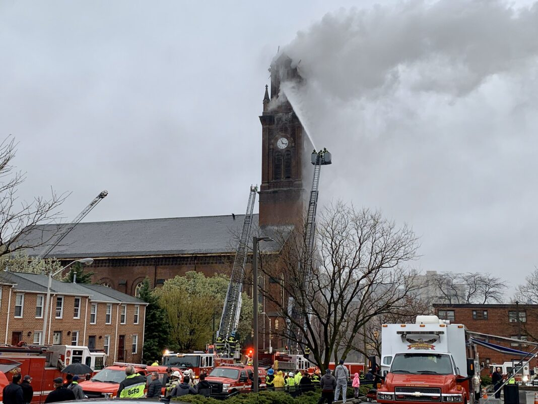 Firefighters in tower ladder put water on fire in Baltimore church