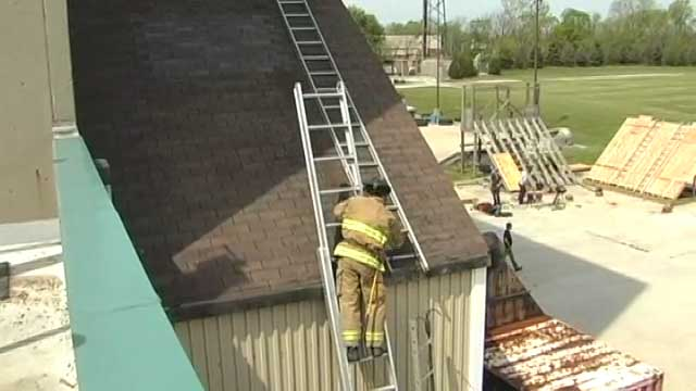 Firefighters on a ladder positions another ladder on the roof