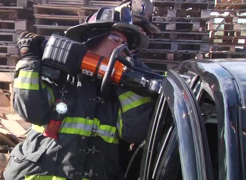 Firefighter with extrication tool attacking B post of vehicle