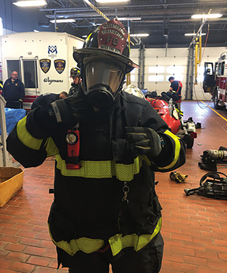 A firefighter with full PPE in zero visibility.