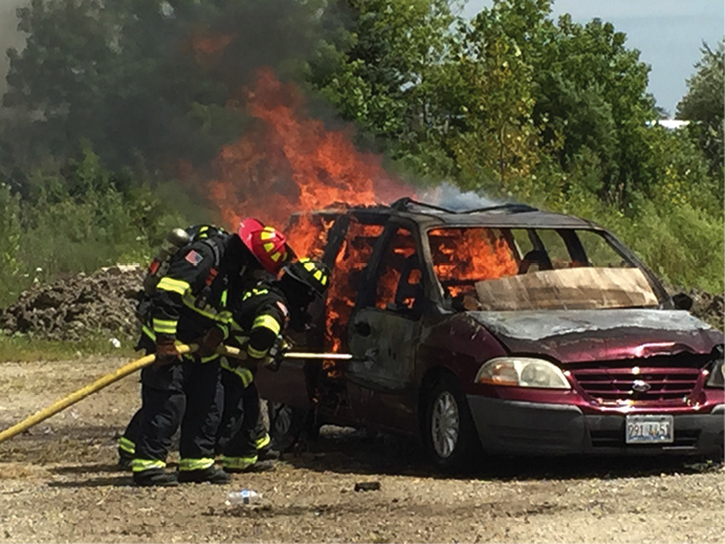 Firefighters attack a vehicle fire
