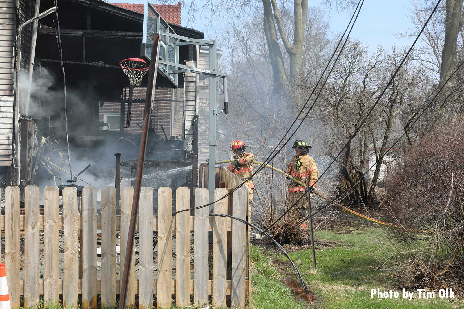 Firefighters administer water on the exterior of the fire