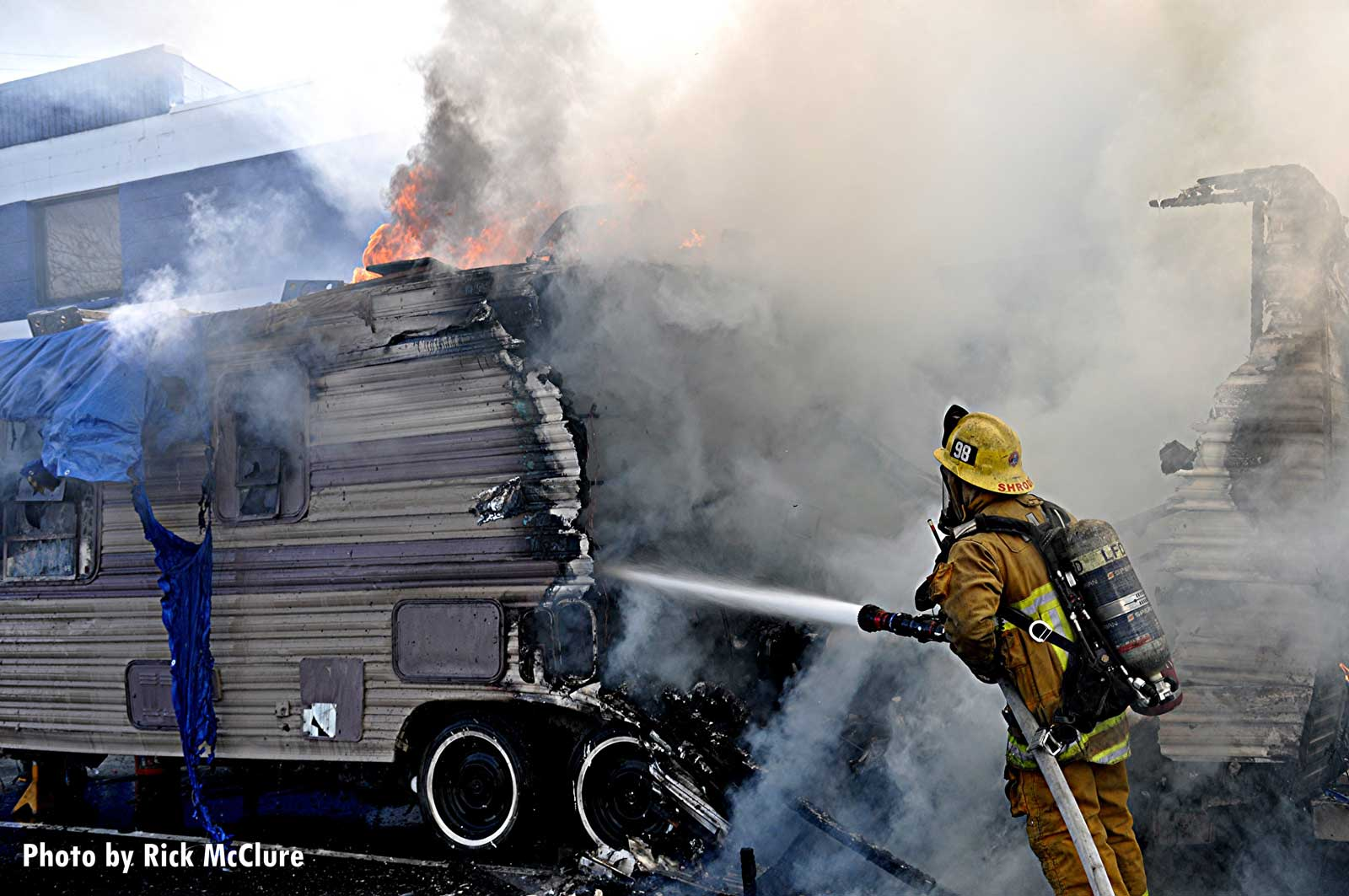 Firefighter applies water to burning trailer
