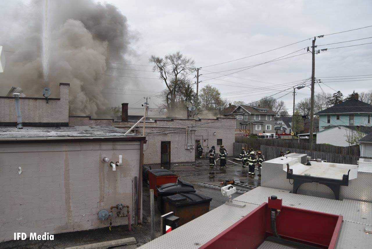 Firefighters and apparatus on a different side of the fire building