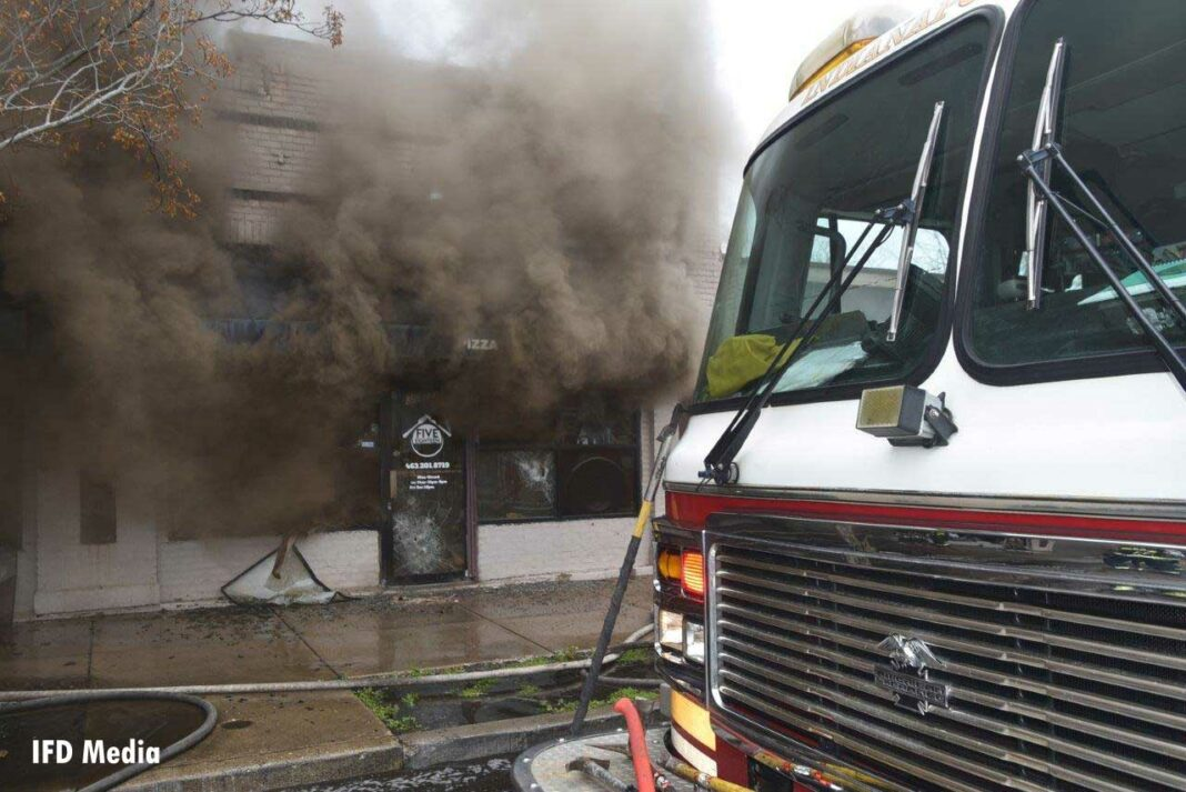 A fire apparatus with heavy smoke condition pushing from building