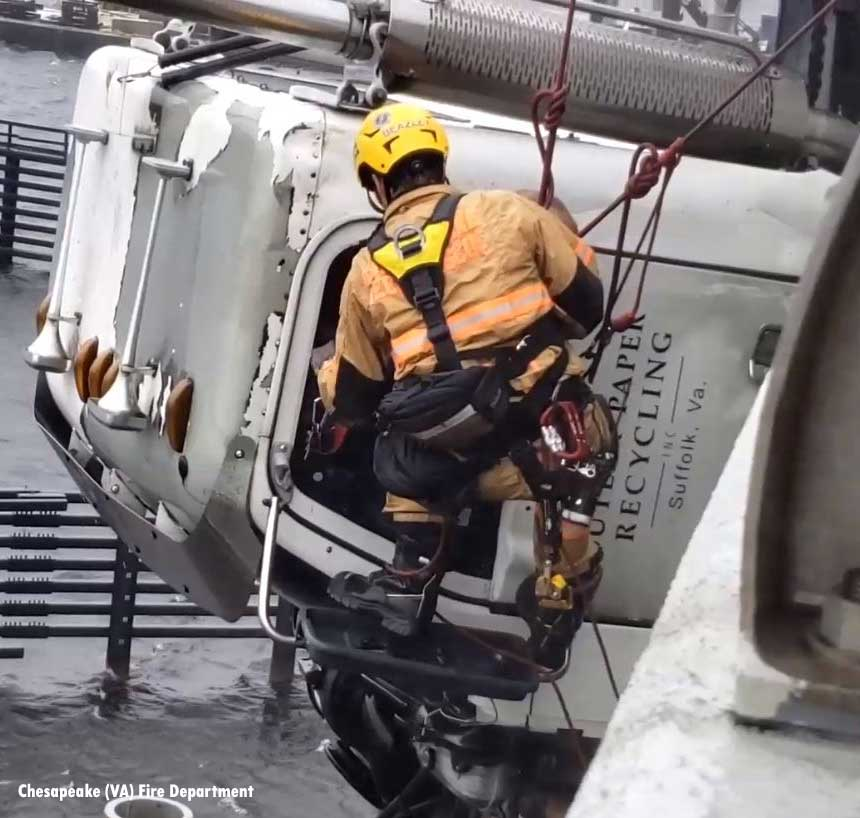A firefighter is lowered to remove the driver from the cab