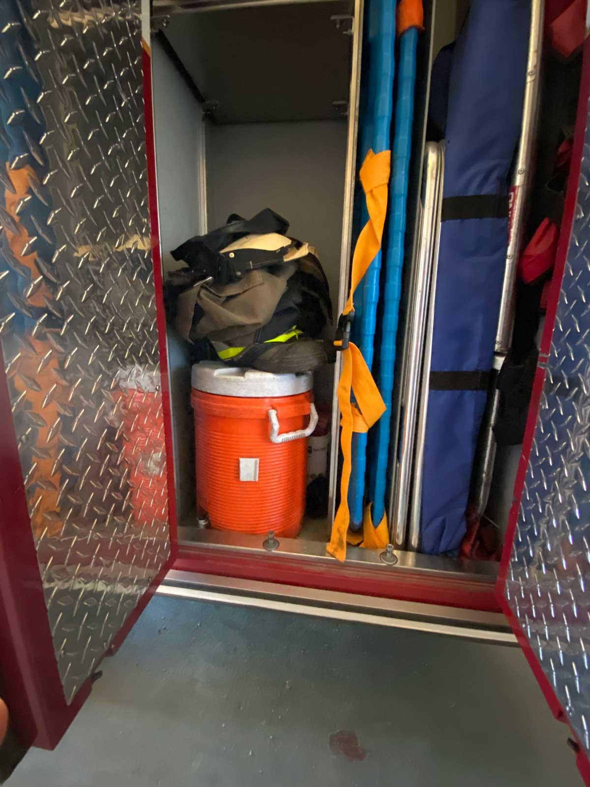 More firefighter gear inside a fire truck compartment