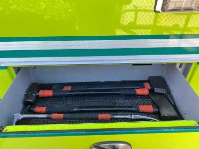 Firefighting tools including a halligan, ax, and sledgehammer inside a compartment on a fire truck