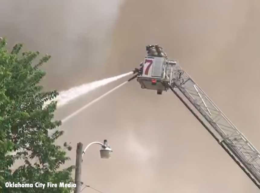 Firefighters in a tower ladder bucket pour water on the flames