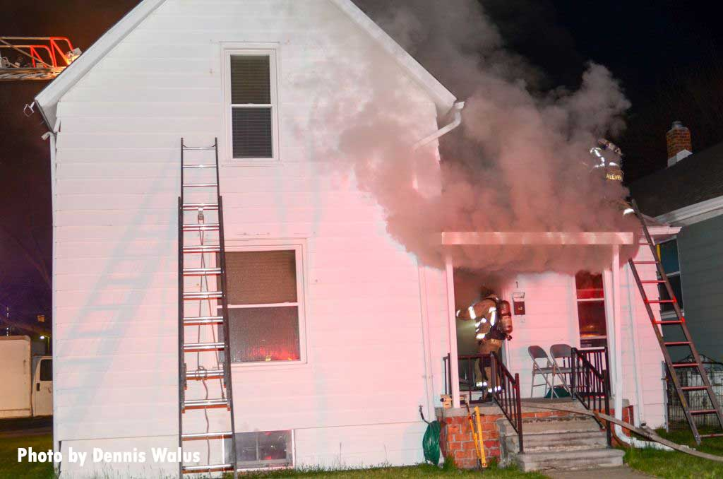Firefighter raise a ladder at a house fire