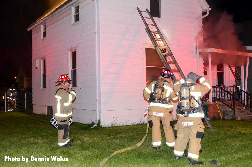 Firefighters with a ladder at a Royal Oak house fire
