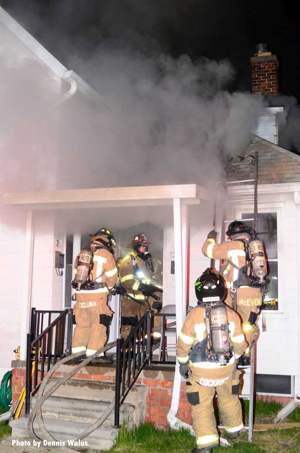 Firefighters at the door during a house fire with smoke