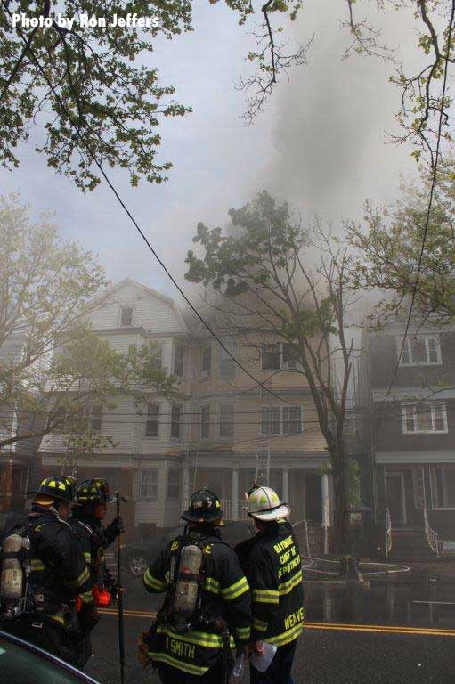 Firefighters working at the smoke-filled fire scene