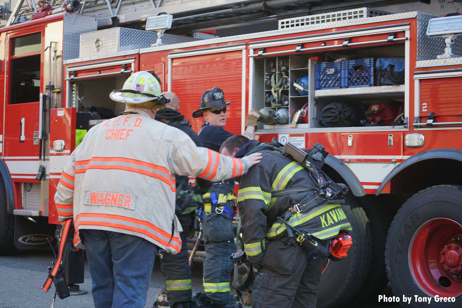 A firefighter hunched over on the fireground surrounded by other firemen