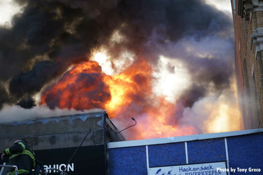 Massive flames shoot through the roof of the building in Hackensack