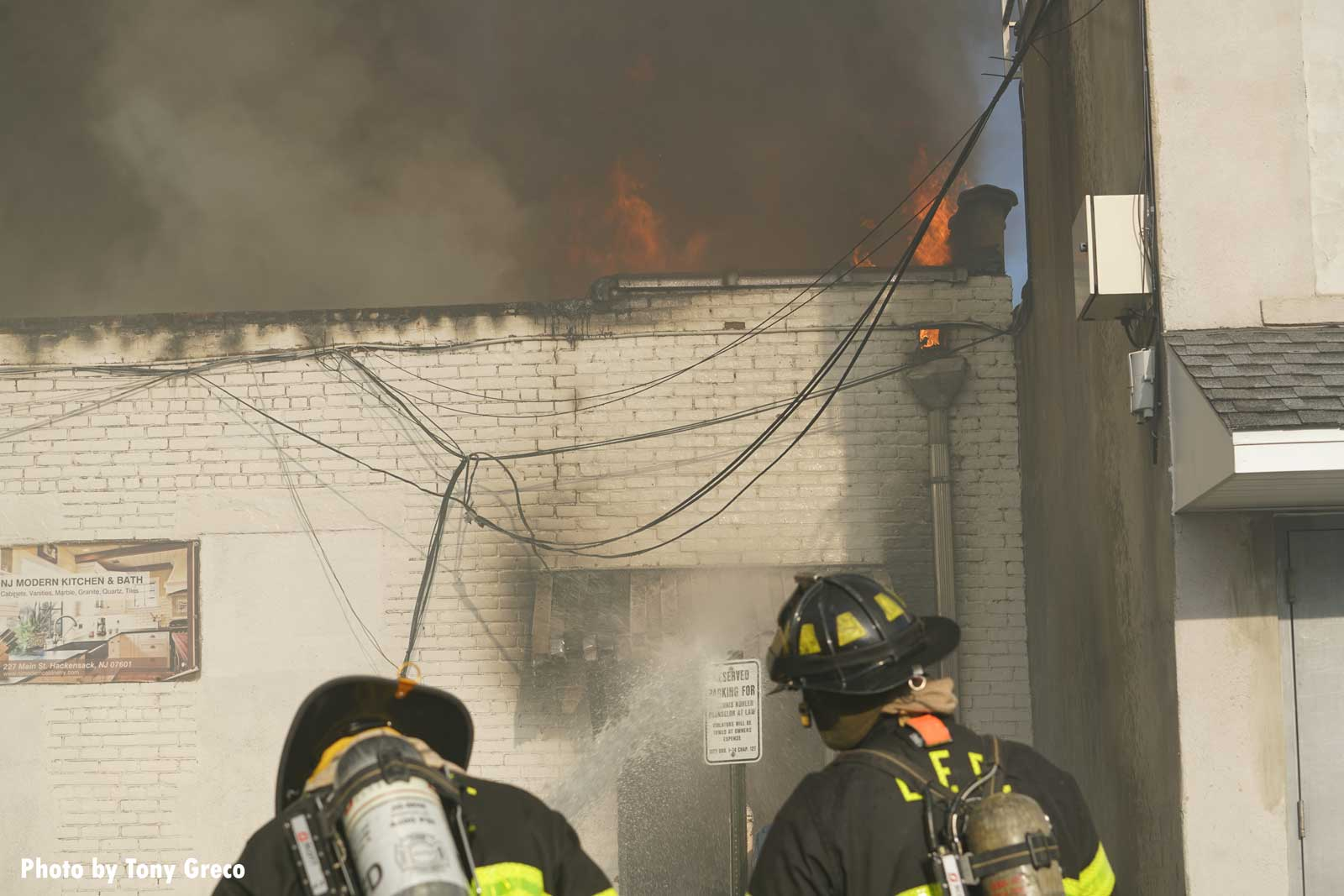 Firefighters confront flames shooting through the roof of the building
