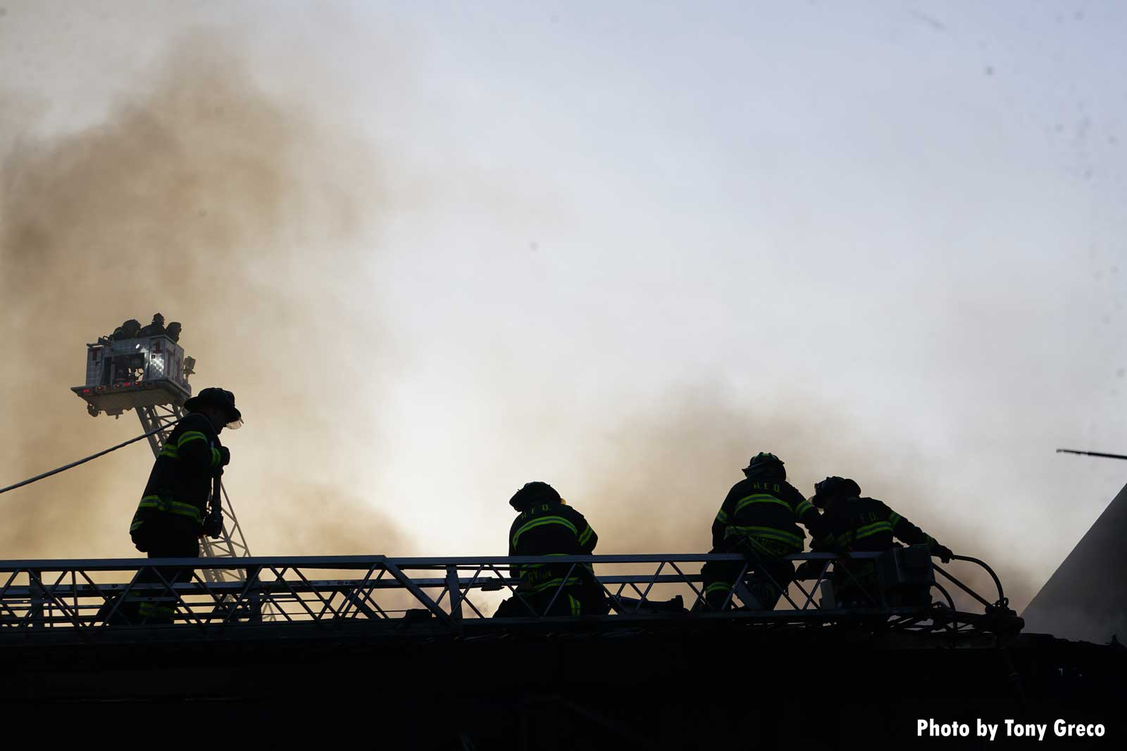 Firefighters on an aerial device with smoke in the background