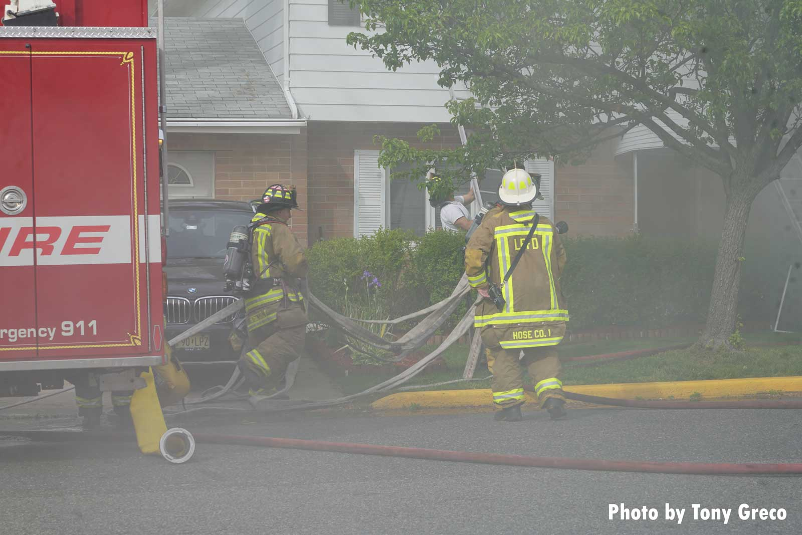 Firefighters pull lines at the house fire