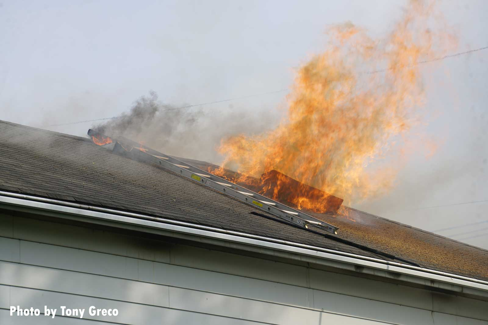 Flames vent from the roof during the Moonachie house fire
