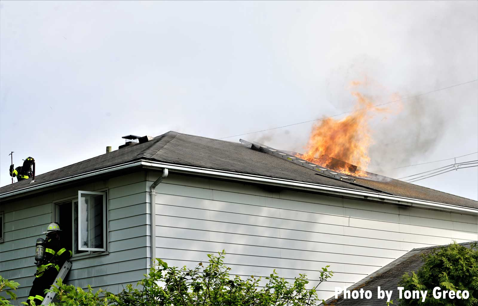 Firefighters operate at a house fire as flames show through the roof