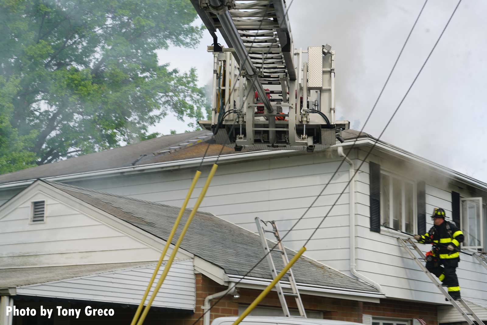 A tower ladder bucket with firefighters on ladders at the house fire