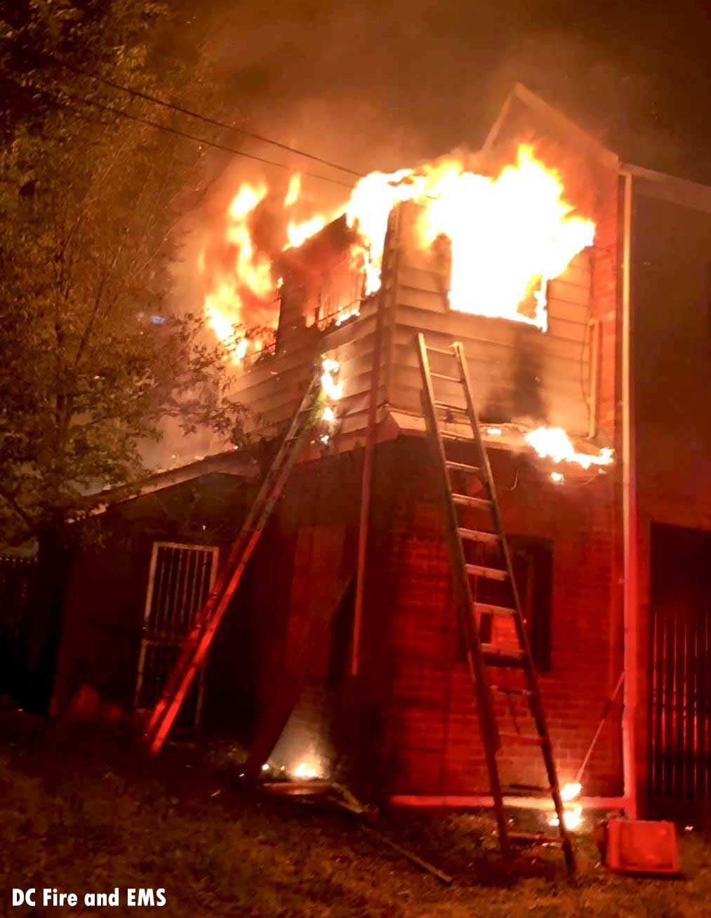 View of a ladder and massive flames venting from a building in D.C.