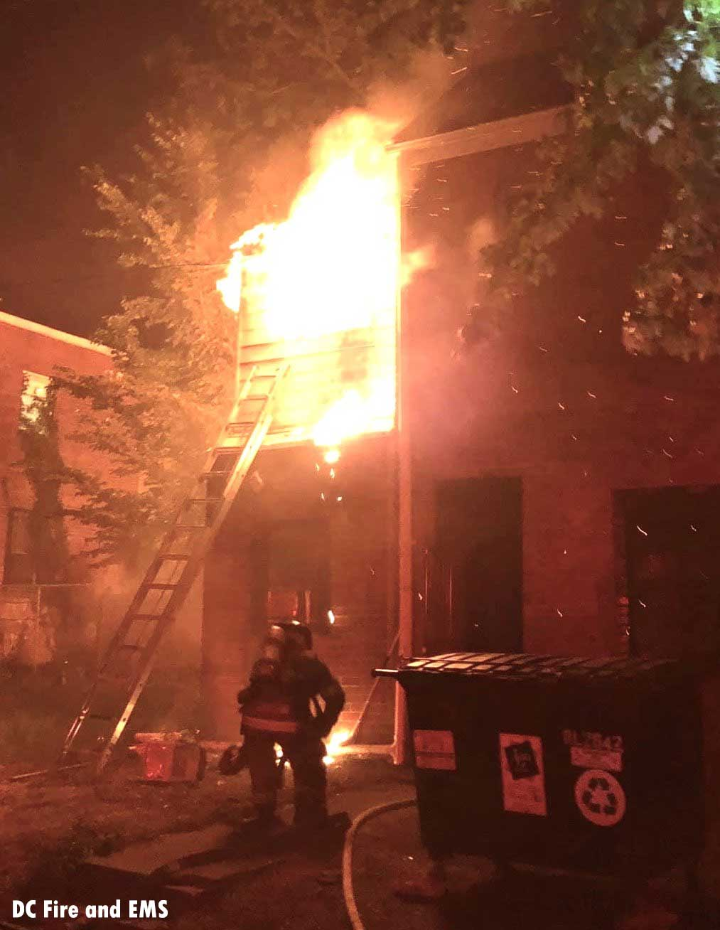 A D.C. firefighter advances toward a building as flames shoot from it