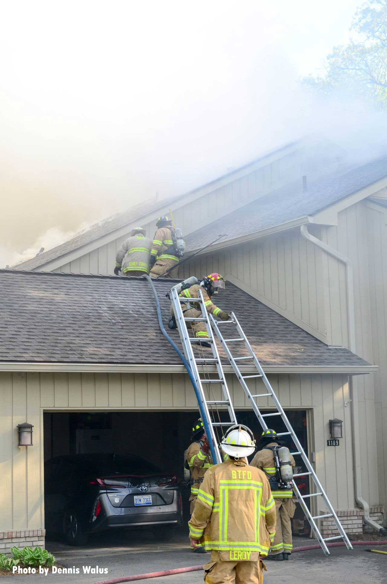 Firefighters raise two ladders at the scene of a fire in Bloomfield, Michigan