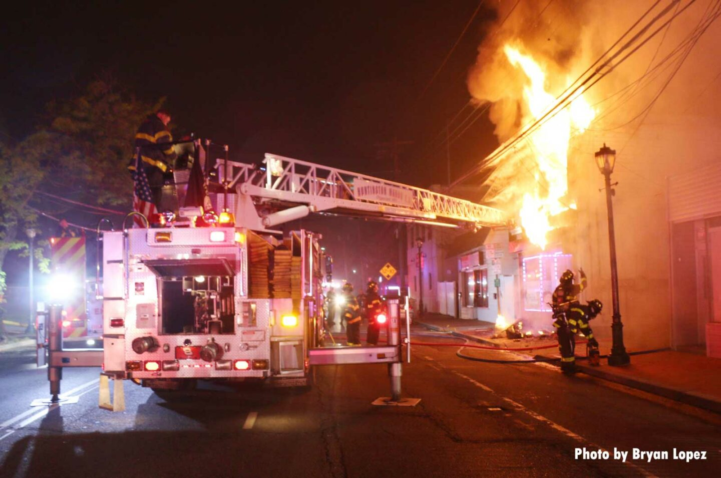 Aerial device extended toward burning building with firefighters working and visible flames