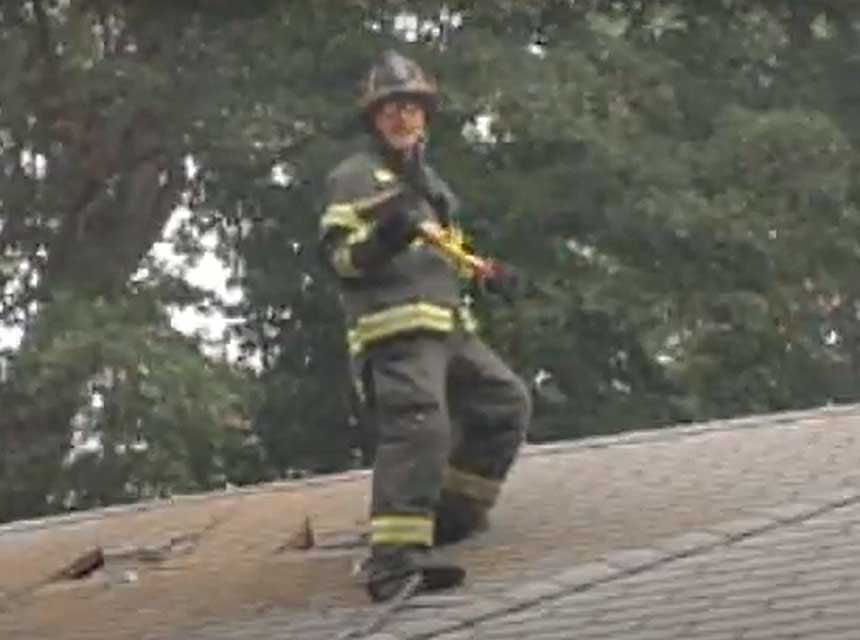 Mike Ciampo on the roof holding an ax