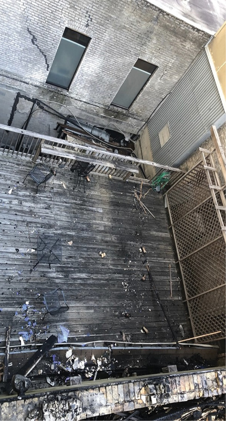 The deck on the C side where Truck 1 had a safe refuge. A closer look reveals the removed portion of the railing the crew had to climb to a storage room roof attached to the C exposure. This storage room roof is the surface from which Truck 9 lowered a 24-foot ladder to allow Truck 1 to climb to safety.