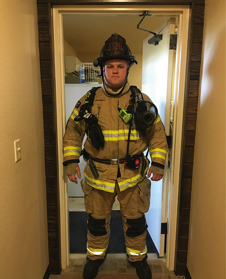 A firefighter stands in a doorway in gear. Note the clearance issue at his shoulders because of the gear.