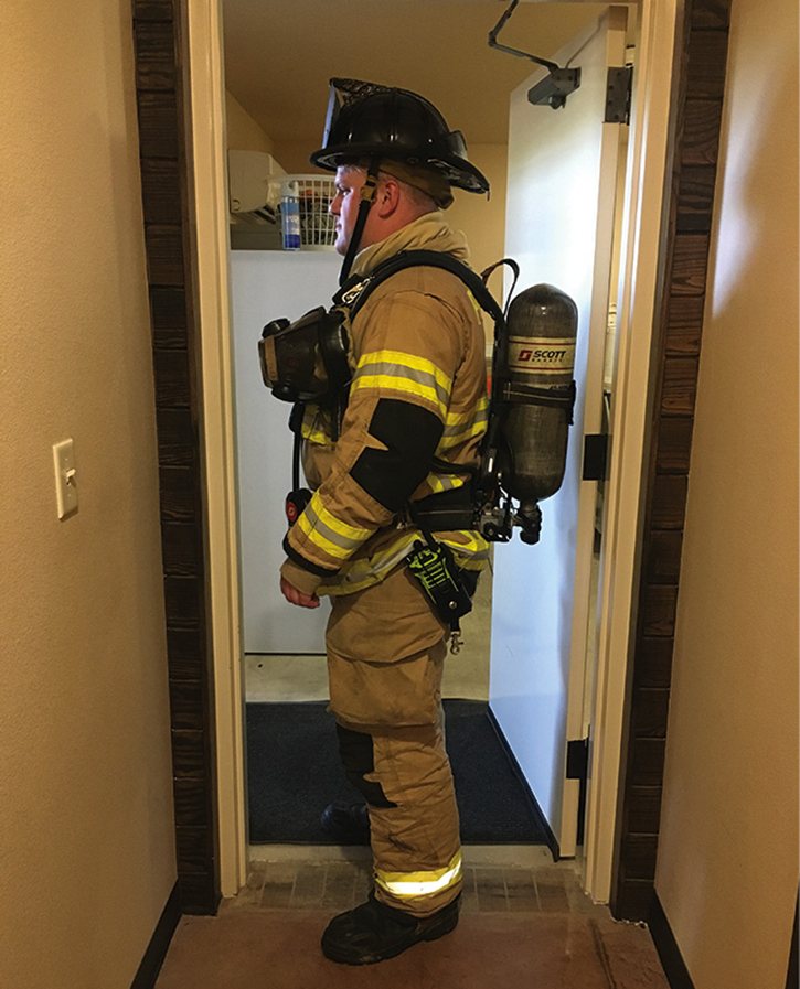 In the same doorway, the firefighter's self-contained breathing apparatus (SCBA) is causing a choke point.