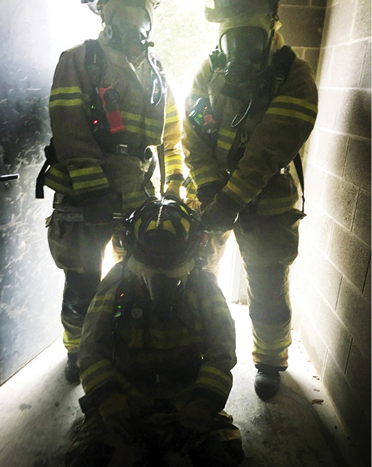 Two firefighters with a tool dragging a down firefighter down the hallway. Note the clearance issue.
