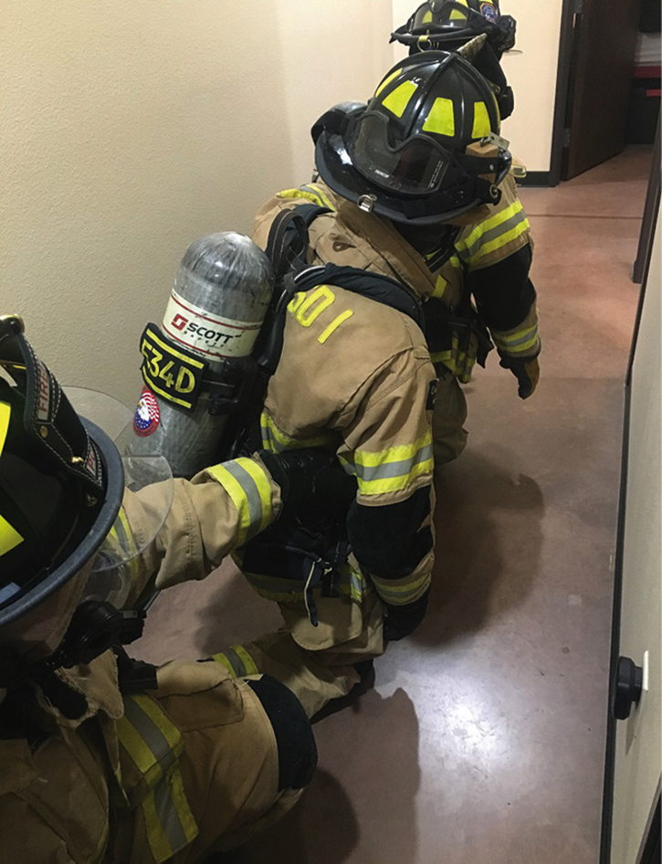 Rescuer 1 grabs Rescuer 2's SCBA, completing the Mule Train.