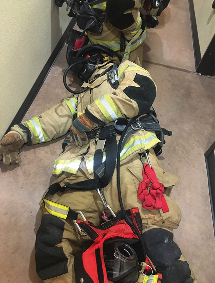 A rapid intervention team (RIT) pack is secured between the down firefighter's legs with the RIT strap looped through the SCBA waist strap.