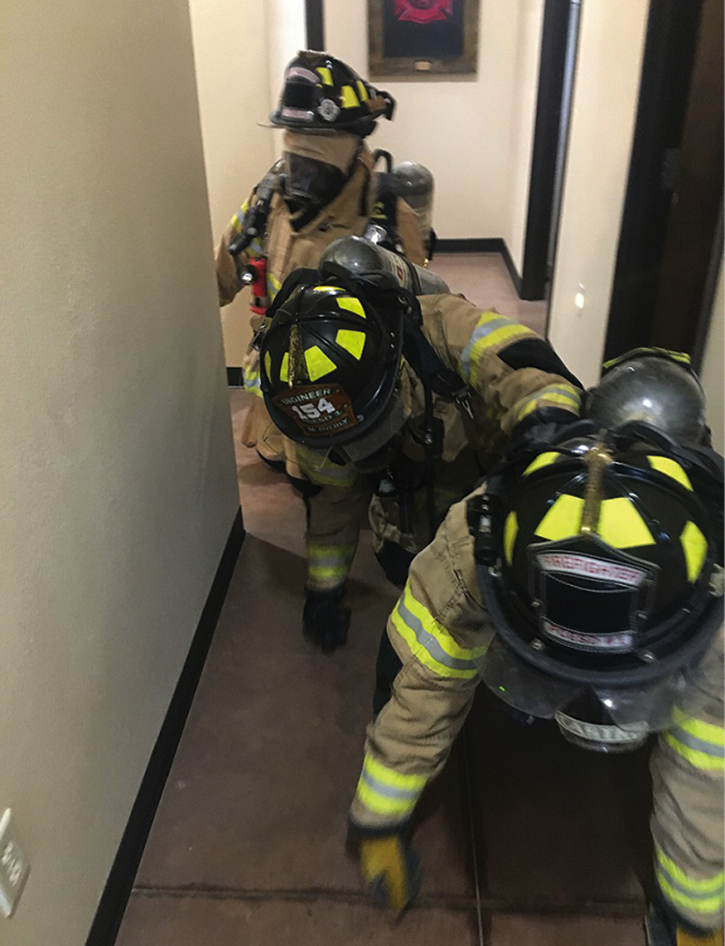 Rescuer 2 grabs Rescuer 3's SCBA, adding another member to the Mule Train.