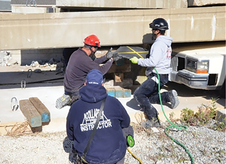 Students in the 56-hour Illinois Fire Service Institute Structural Collapse Rescue Technician course performing a bridge beam lift with a trapped vehicle underneath, the lift used to rescue the worker in this incident.