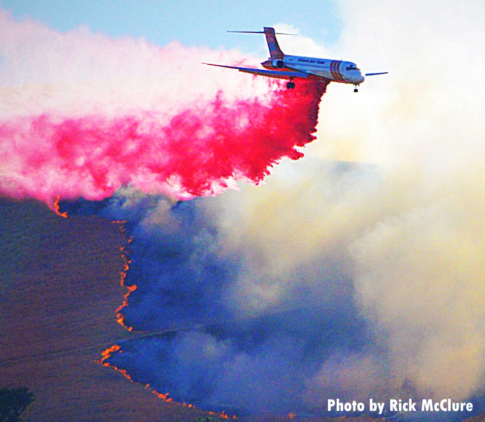 Air tanker drops fire retardant on smoky fire
