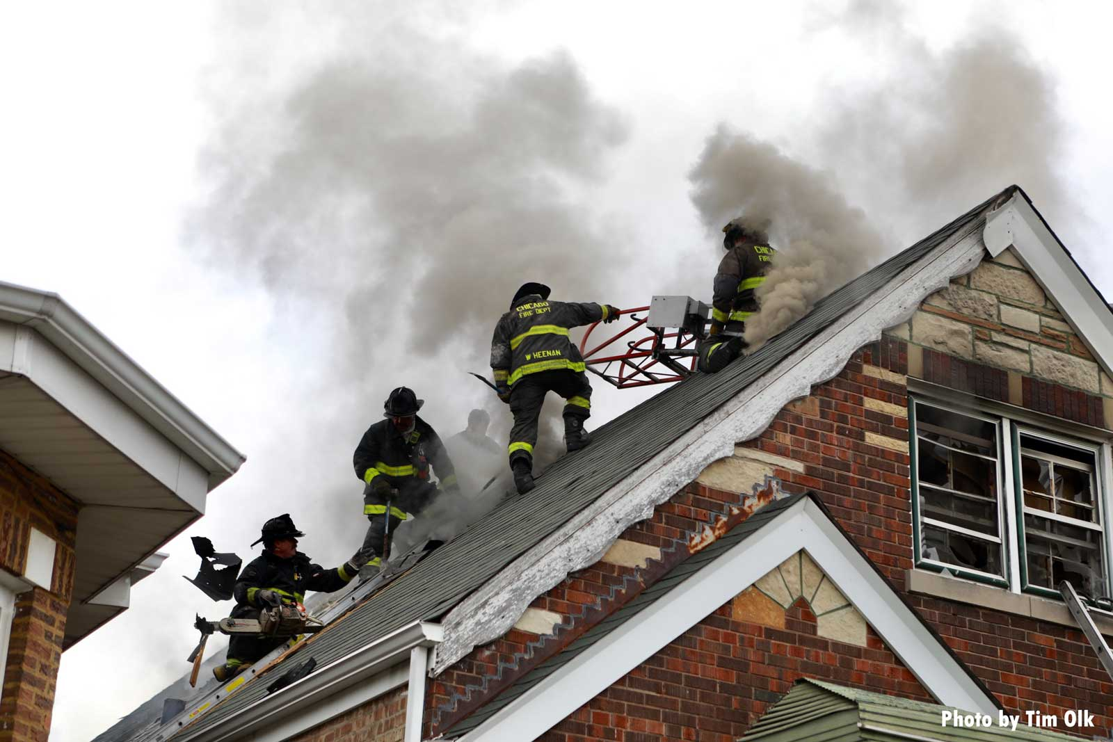 Multiple Chicago firefighters working on the roof of a home