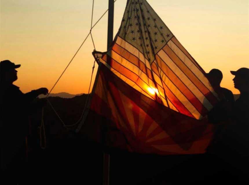 Firefighter raise a U.S. flag