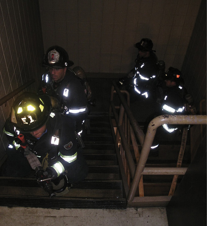 Firefighters advancing up a stairwell