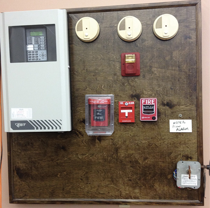 We built a fully functioning alarm system training unit complete with a working panel, four smoke detectors, three pull stations, a water flow alarm, and a working valve alarm. It was cheap, and the only thing we had to buy was the wood mount. A local alarm company did the wiring and testing for us.