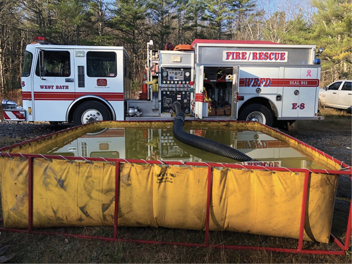 An engine company practicing rural water-supply operations using portable tanks.