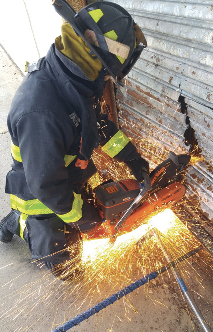 Truck company members drill on rotary saw operations on a commercial building.