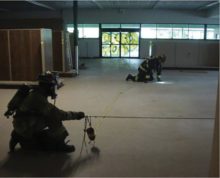 Firefighters practice search rope skills in an empty box store setting