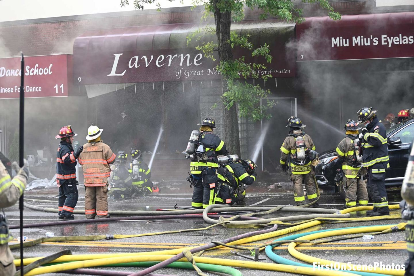 Firefighters work at the scene of a fire that destroyed a row of businesses on Long Island
