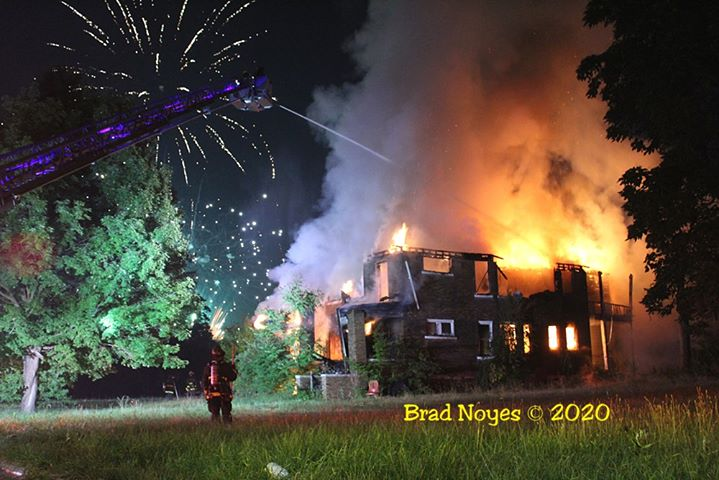 Detroit fire crews at scene of fire with fireworks above