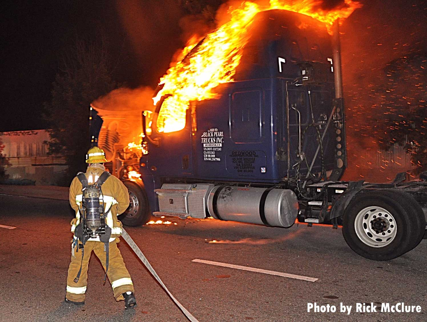 A Los Angeles firefighter with a hoseline at a burning big rig